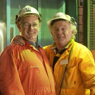 Two grey haired men wearing orange overalls and helmets who are working as volunteers at ERIH Anchor Point Big Pit: National Coal Museum World Heritage Site, Blaenavon, UK
